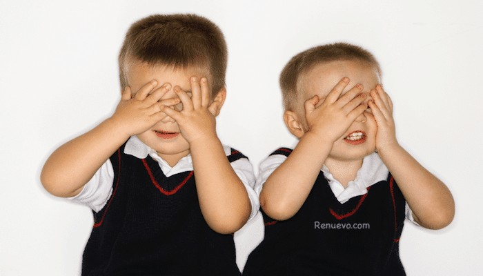 Male twins with hands over eyes. @ iofoto